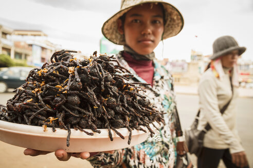 Cambodia, Woman selling fried tarantula spiders - MBE000708