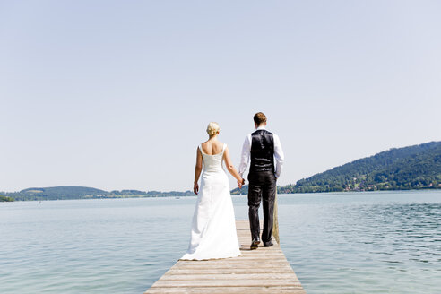 Germany, Bavaria, Tegernsee, Wedding couple standing on jetty - RFF000086