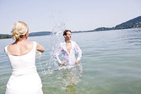 Germany, Bavaria, Tegernsee, Wedding couple standing in lake, pouring water over groom - RFF000090