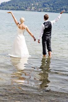 Germany, Bavaria, Tegernsee, Wedding couple standing in lake, wearing hand cuffs - RFF000106