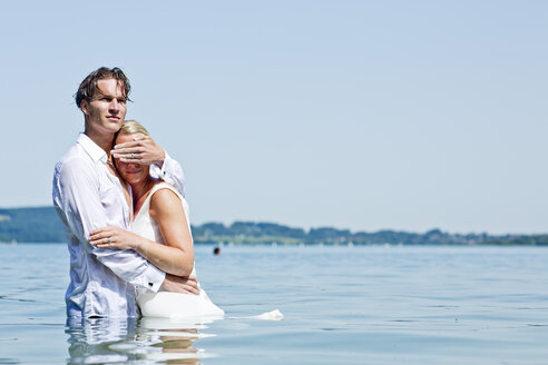 Germany, Bavaria, Tegernsee, Wedding couple standing in lake, man shielding woman's eyes - RFF000097