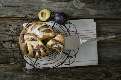 Homemade prune cake with cooling rack and cake server on wooden table, close up - OD000331