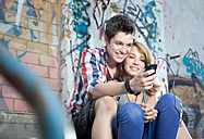 Germany, Berlin, Teenage couple using mobile phone, smiling - MVC000008