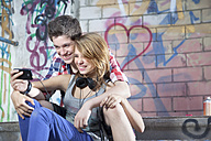 Germany, Berlin, Teenage couple using mobile phone, smiling - MVC000011