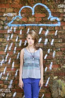Germany, Berlin, Portrait of teenage girl standing in front of wall with graffiti - MVC000019