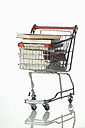 Stack of books in shopping cart on white background, close up - ASF005111