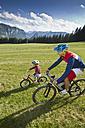 Germany, bavaria, Chiemgau, Father and son biking in meadow - FF001372