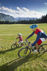 Germany, bavaria, Chiemgau, Father and son biking in meadow - FF001372