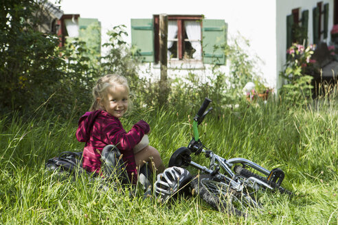 Germany, bavaria, Inzell, Girl sitting in meadow with bicycle, smiling - FF001375