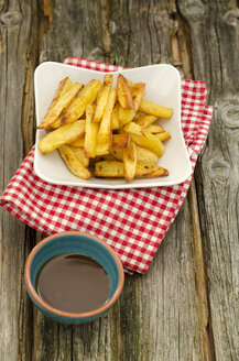 Homemade french fries with curry sauce on wooden table, close up - OD000341