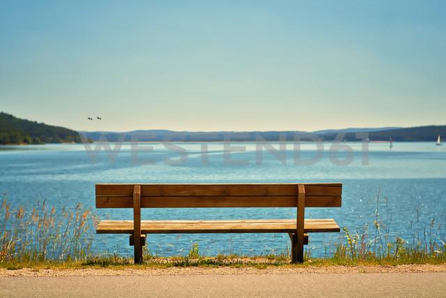 Germany, Bavaria, View of empty bench at coast - DIKF000070