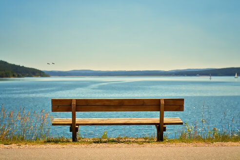 Germany, Bavaria, View of empty bench at coast - DIKF000070