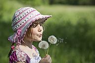 Germany, Bavaria, Girl blowing dandelion - STB000035