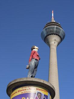 Germany, North Rhine Westphalia, Duesseldorf, Woman looking at Rheinturm Rhine tower - HHE000065