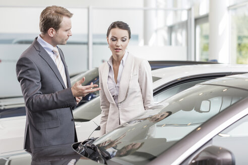 At the car dealer, Salesman showing new car to client - MLF000035