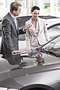 At the car dealer, Salesman showing new car to client - MLF000037
