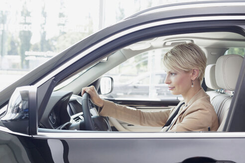 At the car dealer, Woman sitting in new car - MLF000050