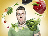 Young man looking at flying vegetables, Composite - STKF000351