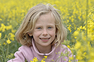 Germany, Baden-Wuerttemberg, Swabian Alps, Portrait of young girl sitting in a field of rape - CR002479