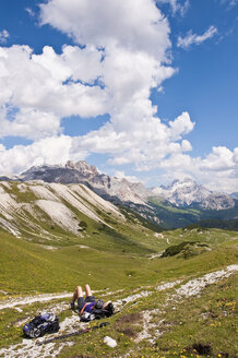 Italy, South Tyrol, Dolomites, Fanes-Sennes-Prags Nature Park, hiker lying in alpine meadow - UM000642