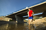 Germany, Baden-Wuerttemberg, Winterbach, athletic young man running through Rems river - STSF000116