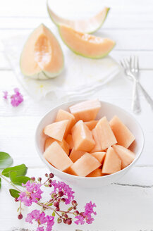 Pieces and slices of charentais melon on white wooden table - CZF000080