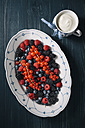 Berries on serving plate with cup of yoghurt - EC000308