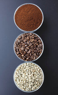 Three bowls with ground coffee, roasted and unroasted coffee beans - JT000493