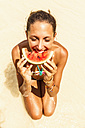 Thailand, Koh Surin Island, woman eating a slice of watermelon at the beach, close-up - MBEF000733