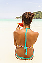 Thailand, Koh Surin island, woman eating a slice of watermelon at the white sandy beach - MBEF000734
