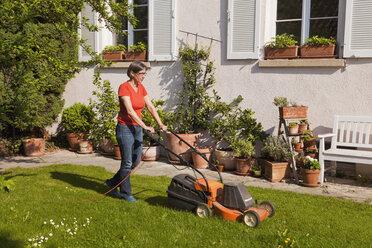 Germany, Stuttgart, Woman mowing lawn - WDF001930