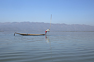 Myanmar, Lake Inle, Fisherman on boat hitting water surface with wooden stick - DR000174