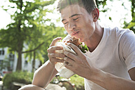 Young man eating hamburger - FEXF000035