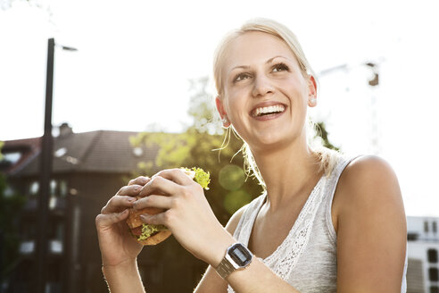 Smiling young woman with hamburger - FEXF000038
