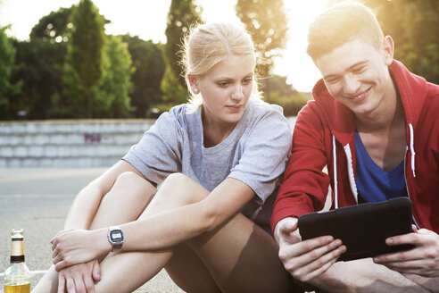 Young couple with tablet pc sitting on ground - FEXF000029