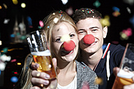 Germany, North Rhine Westphalia, Cologne, young couple with clowns noses toasting - FEXF000003