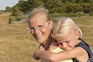 France, Bretagne, Landeda, Mother carrying daughter piggyback - LAF000128