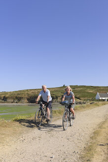 France, Bretagne, Finistere, Senior couple on e-bikes at the coast - LA000149