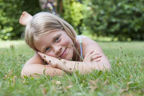 Smiling girl lying in grass - NHF001421