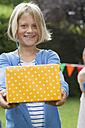 Girl handing over birthday present - NHF001441