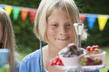 Girl looking at muffins on a birthday party - NHF001469
