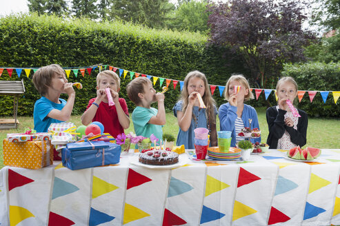 Children using party blowers on a birthday party - NHF001443