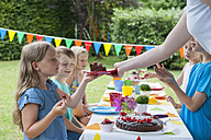 Girl receiving piece of cake on a birthday party - NHF001450