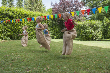 Children having a sack race in garden on a birthday party - NHF001462