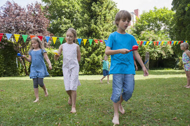 Children having a spoon and egg race in garden on a birthday party - NHF001458