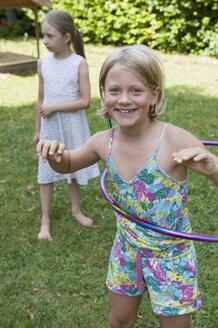 Happy girl with hula hoop in garden - NHF001457