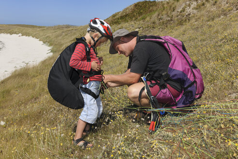 France, Bretagne, Landeda, Father and son with paraglider in dune - LAF000169