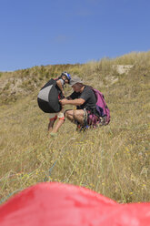 France, Bretagne, Landeda, Father and son with paraglider in dune - LAF000161