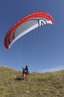 France, Bretagne, Landeda, Father and son with paraglider in dune - LAF000163
