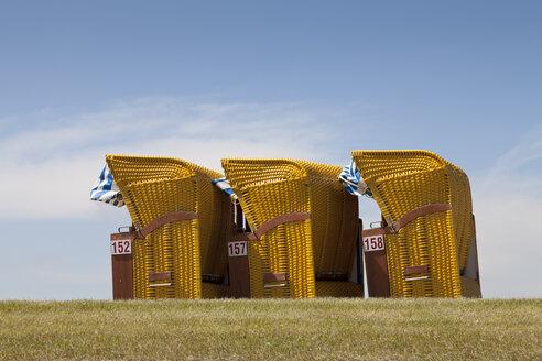Germany, Lower Saxony, Eastern Friesland, Butjadingen, Burhave, three roofed wicker beach chairs - WIF000042